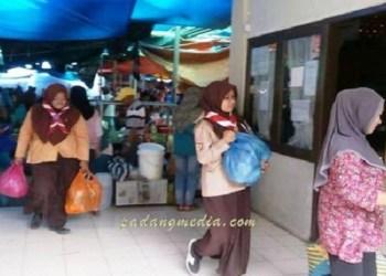 Anggota Pramuka Kwarcab Sawahlunto membantu membawa barang belanjaan pengunjung di Pasar Sawahlunto, Rabu (21/6). (tumpak)