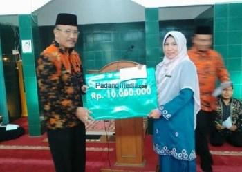 Kepala MA KMM Kauman Padangpanjang, Derliana, MA menerima bantuan dari Kanwil Kemenag Sumbar. (foto: humas)