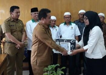 Sekda Padangpanjang menyerhkan bantuan Baznas Padangpanjang kepada mustahiq. (foto: humas)