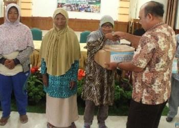 Warga menerima bantuan paket sembako dari Dinas Sosial Mentawai. (ers)
