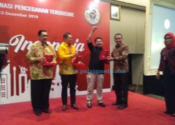 Direktur Pencegahan BNPT Brigjen Pol Hamli menyerahkan plakat kemenangan kepada Ketua FKPT Sumbar Dr. Zaim Rais didampingi ketua FKPT Kalsel dan Ketua FKPT Jateng.