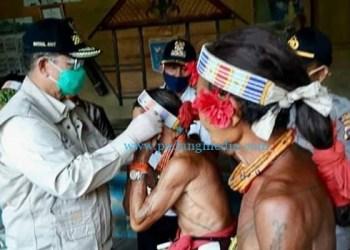 Wagub Sumbar Nasrul Abit memasangkan masker kepada masyarakat di Mentawai. (ist)