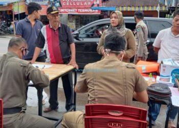 Petugas penegakan Perda AKB sedang mendata pelanggar prokes dalam operasi yustisi yang digelar di Pasar Inpres Painan, Kamis (22/10/2020). (Dok. Humas Setkab Pessel)