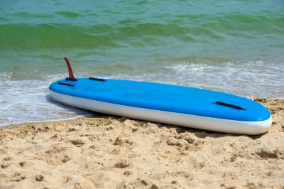 Inflatable standup paddleboard iSUP upside down on the beach