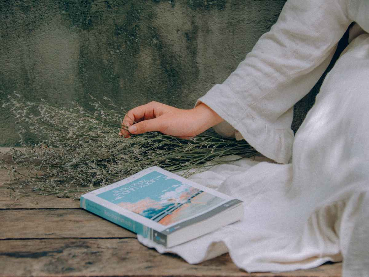 blue and white book beside woman wearing white dress