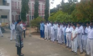 Padmini in a black and white dressing speaking with Indian physical education teachers under training at RKMVU's APE Program