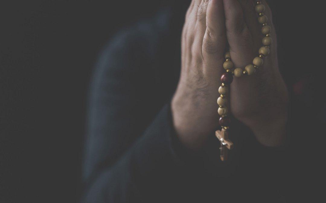pessoa a rezar com terço na mão