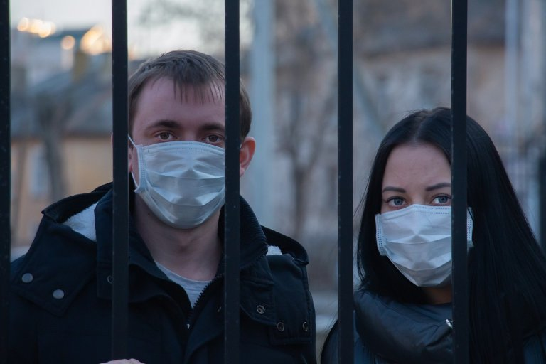 mit Maske hinter Gittern
