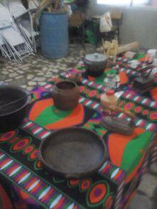 Detalhe da mesa da culinária: panelas de ferro, lamparinas.