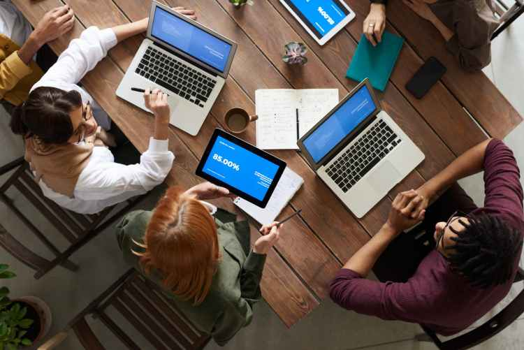 top view photo of group of people using macbook while discussing