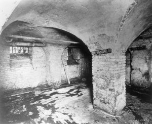 Image depicting a prison cell built in 1800 with brick column and vaulted arches with dilapidated floor and crumbling brick walls