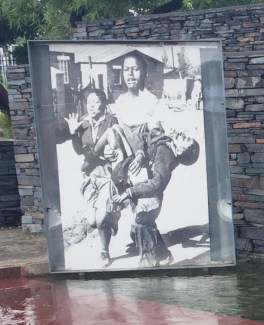 Hector Pieterson being carried by Mbuyisa Makhubo. His sister, Antoinette Sithole, runs beside them.