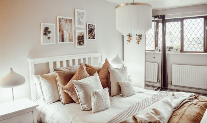 Bedroom view featuring white bedroom furniture, mirrored wardrobes, a hanging chandelier light, and the bed dressed with lots of cushions and throws.
