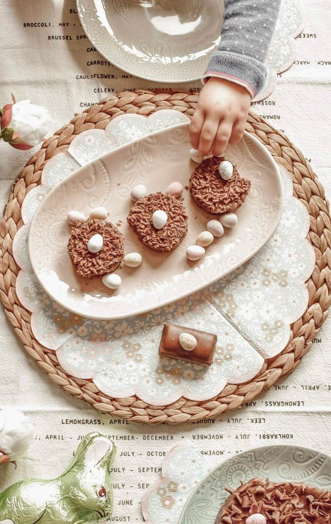 image from above of crockery on a table displaying chocolate treats and a young girls hand reaching to take something from a plate