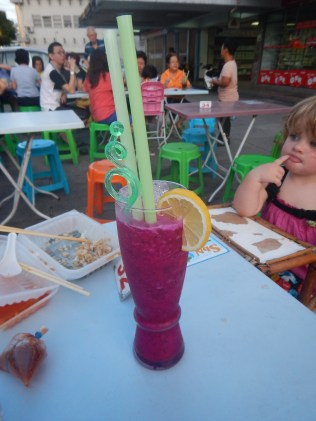 Street food in Penang. Dragonfruit shake, with the remnants of a fried oyster omelette.