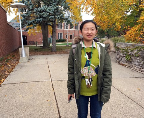 Junior Zhimin Zhang wears a bright green sweater layered over a collared shirt as she walks from her class in Ronan Hall. Zhang is an international student from Inner Mongolia who currently takes courses in the English Language Institute at Central Michigan University.