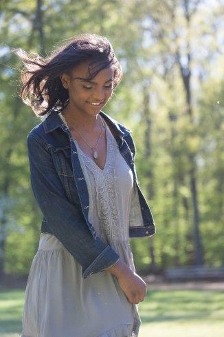 Teen girl twirling in a dress on a field