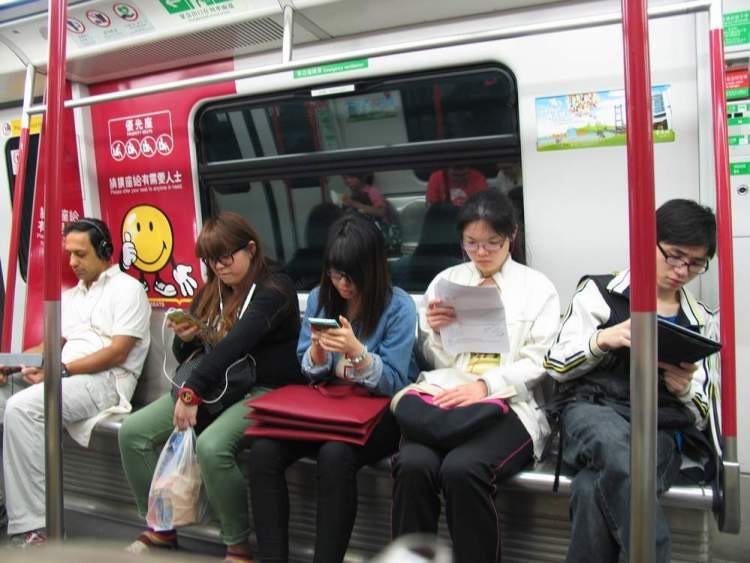 пассажиры в вагоне метро Гонконка с гаджетами