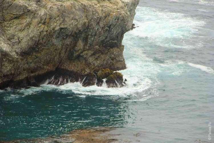 Волны ударяют о скалу