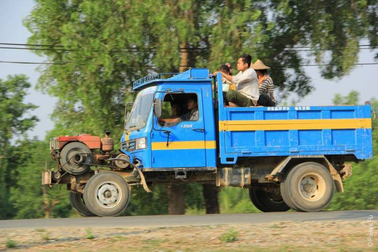 Синий грузовик едет по дороге