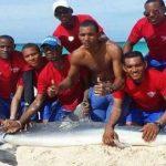 Grupo de homens tira foto em cima de um tubarão que morreu após ser retirado da água, em Punta Cana na República Dominicana