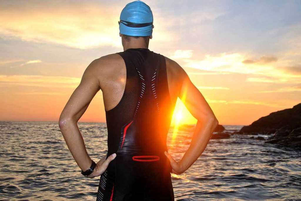 triathlete in wetsuit looking at water