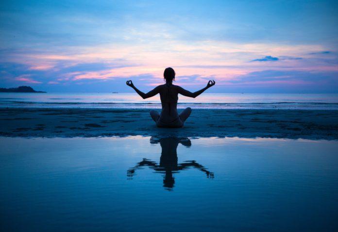 woman sitting on beach doing yoga