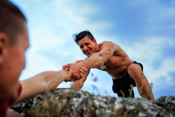 strong man helping another man climb a mountain