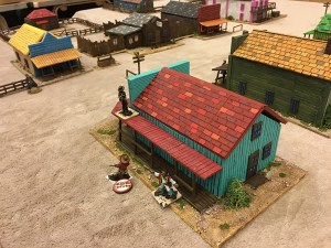 The Outlaws exit the saloon to attack the Pinkertons