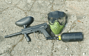 paintball gun and mask on asphalt