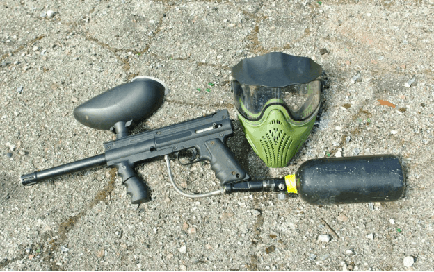 paintball gun and mask on asphalt