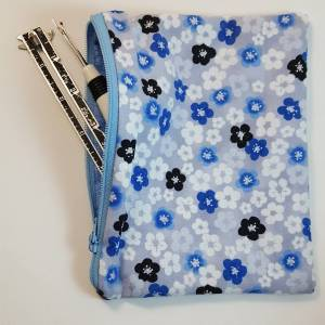 rectangular zipper pouch in blue floral fabric, unzipped with sewing tools halfway inside it.