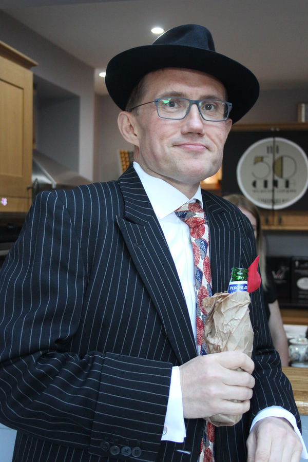 1920s gangster drinking beer in brown bottle at speakeasy party