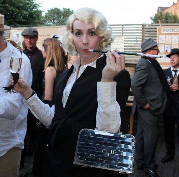 Gangsters moll with cigarette in holder at speakeasy party.