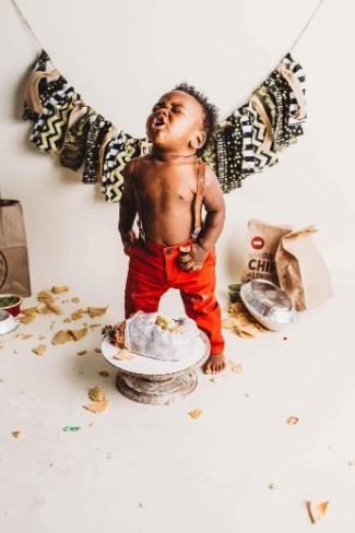Toddler boy standing over smash cake