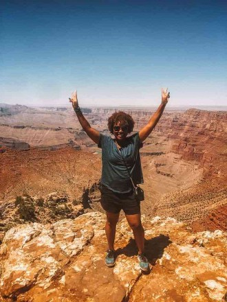 Blogger at grand canyon holding up peace sign