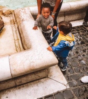 Two toddlers playing at Trevi Fountain