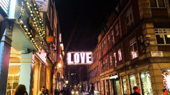 Love sign hanging in the streets of London at night.