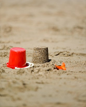 Red bucket in sand at the beach