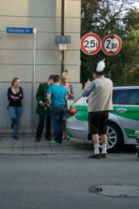 A men in lederhosen takes picture of people in uniforms...only in Germany