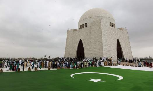 People gather near a national flag during a ceremony to celebrate the country's 69th Independence Day at the mausoleum of Muhammad Ali Jinnah in Karachi, Pakistan, August 14, 2015. Jinnah is generally regarded as the founder of Pakistan. REUTERS/Akhtar Soomro