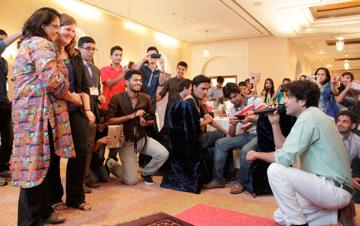 Pakistani Pop Singer Shehzad Roy serenading U.S Embassy's Cultural Affairs Attaché Jennifer McAndrew and iEarn Pakistan Executive Director Farah Kamal