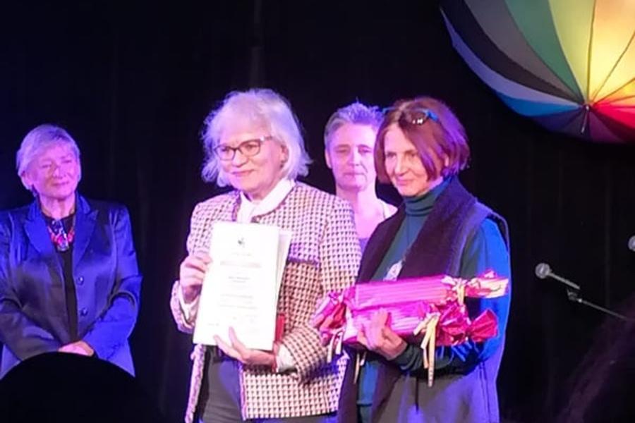 cztery kobiety stojace na scenie, dwi z nich trzymają w rękach nagrody