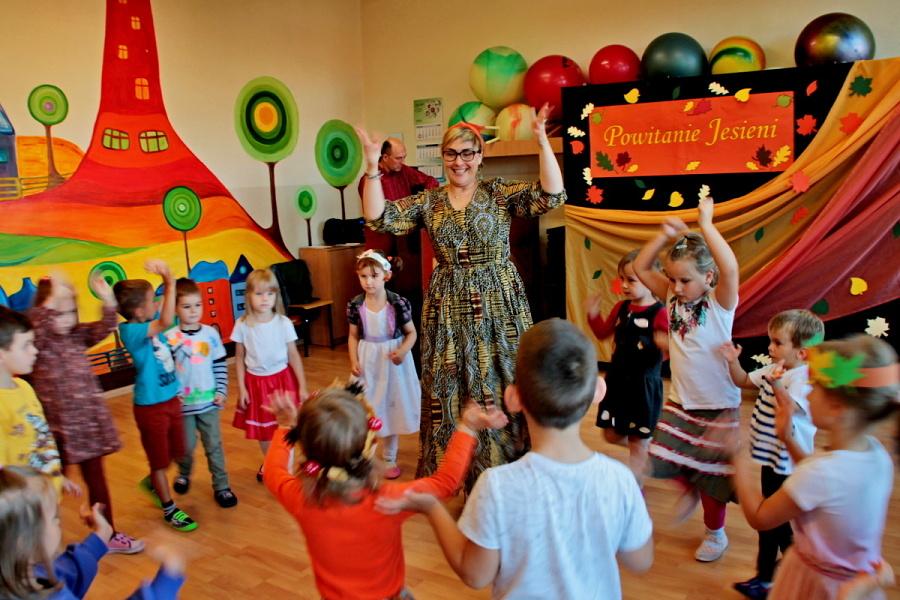 Dzieci z nauczycielką tańczą. W tle napis Powitanie Jesieni