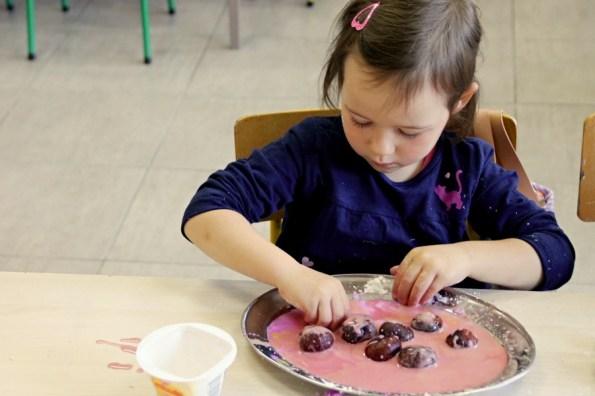 Kilkuletnia dziewczynka macza kasztany wmasie plastycznej koloru różowego