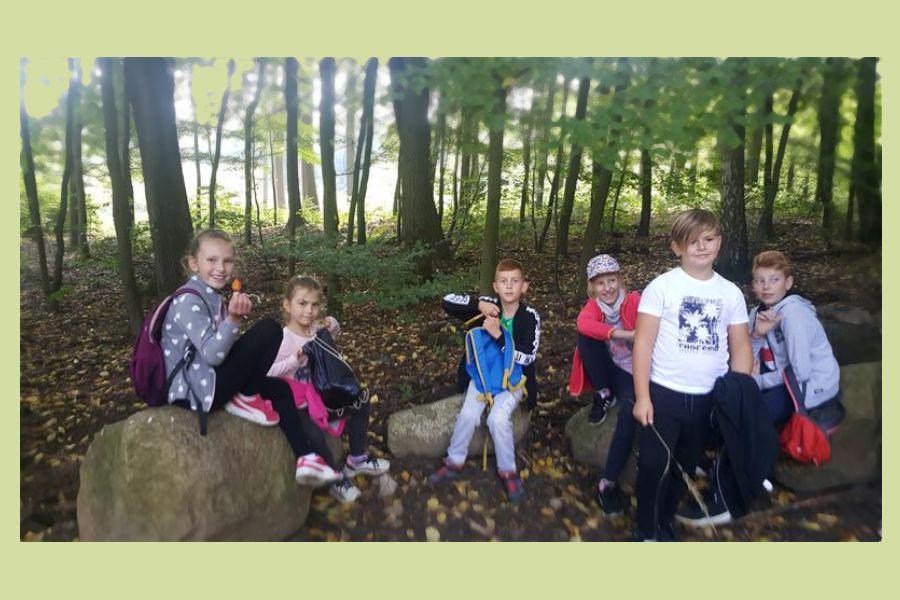 Sześciu uczniów odpoczywa na kamiennych głazach, w tle las.