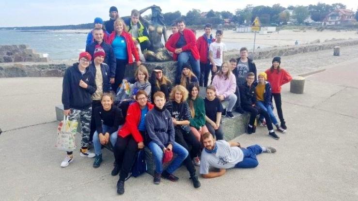 Wspólne zdjęcie uczestników rejsu wraz zopiekunami przy pomniku Usteckiej Syrenki któryznajduje się nafalochronie. Wtle widać fragment morza iplaży