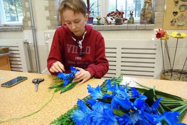 dziewczynka trzymająca koło zrafii doczepia doniego różowe kwiaty iliście tworząc wianek. Nastole płatki niebieskich iróżowych kwiatów.