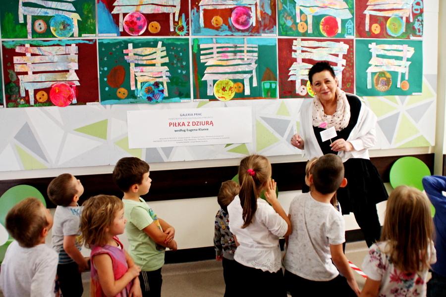 Anna Gielarowska stoi z przedszkolakami przed wystawą ich prac plastycznych