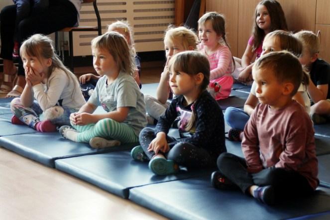 Grupa dzieci - przedszkolaków, siedzą namatach, oglądają przedstawienie